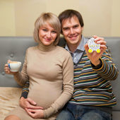 Pregnant couple showing cookie in the form of stroller — Stock Photo