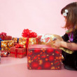 Little child looking at a lot of Christmas gifts or birthday presents — Stock Photo