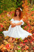 Bride sitting among red leaves — Stock Photo