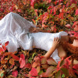 Red-haired young woman lying among red leaves - Stock Photo