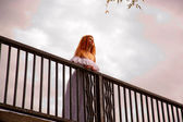 Bride standing on the bridge. Sunset. Bottom view. — Stock Photo