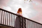 Noiva em pé sobre a ponte. pôr do sol. vista inferior. — Foto Stock