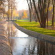 Stream, paved path and benches in the city park — Stock Photo