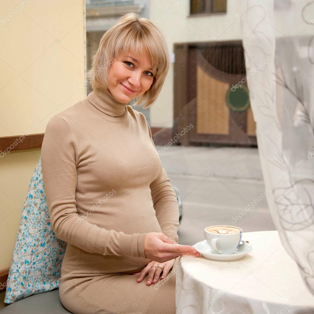 Beautiful young happy pregnant woman having breakfast a cup of cappuccino — Stock Photo #14505831