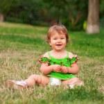 kleines Mädchen sitzt auf dem grünen Gras — Stockfoto