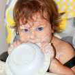 Baby eating yogurt and soiled face, hands, and all around — Stockfoto