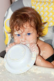 Baby eating yogurt and soiled face, hands, and all around — Stock Photo