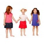 üç sevimli gülümseyen küçük kız elele — Stok fotoğraf