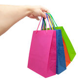 Hand giving colorful paper shopping bags — Stock Photo