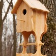Wooden house with a feeding trough for birds - Stock Photo