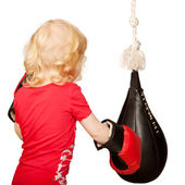 Kid exercising punching bag. — Stock Photo