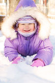 Happy smiling baby lying in the snow — Stock Photo