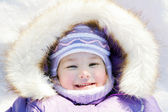 Winter portrait. Happy smiling baby lying in the snow — Stock Photo