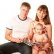 Happy family reading a book and smiling. — Stock Photo