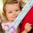 Stock Photo: Happy baby sitting in a carrying sling.