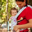Happy baby sitting in a carrying sling. — Stock Photo #18547745