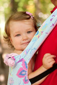 Happy baby sitting in a carrying sling. — Stock Photo