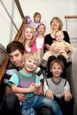 Big happy family sitting on the stairs at home. — Stock Photo