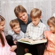 Happy mother and four children reading a book. — Stock Photo