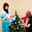 Family decorating a Christmas tree. - Stock Photo