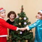 Children dancing around the Christmas tree. — Stock Photo