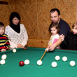 Happy family playing in the billiards. — Stock Photo