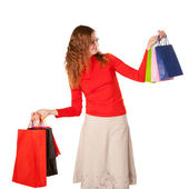 Shopping woman in glasses holding many shopping bags — Stock Photo