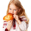 Little girl eating bun with big appetite. — Stock Photo
