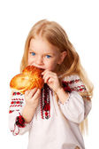 Little girl eating bun with big appetite. — Foto de Stock