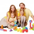 Happy redhead father, mother and two children building from toy  — Stock Photo