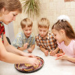 Happy big family cooking a pie together. — Stock Photo #21988521