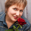 Middle-aged woman with a rose. - Stock Photo