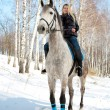 Girl riding on pale horse sunny winter — Stock Photo