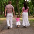 Stock Photo: A young family, father, mother and toddler daughter walking in t