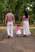A young family, father, mother and toddler daughter walking in t — Stock Photo