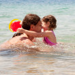 Father and baby daughter playing in the water. - Stock Photo