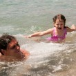 Father and baby daughter playing in the water. — Stock Photo