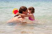 Pappa och baby dotter spelar i vattnet. — Stockfoto
