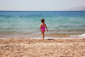 Little girl standing on beach in swimsuit. Rear view. — Stock Photo