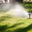 Stock Photo: Lawn sprinkler watering grass