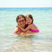 Father and baby daughter embracing and smiling in the sea — Stock Photo