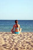 Woman meditating on beach. Rear view. — Stock Photo