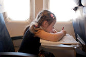Little girl drawing and flying by plane — Stok fotoğraf