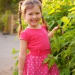 Stock Photo: Little girl with pigtails in the garden
