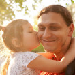 Little daughter kissing father. Happy family outdoors. — Stock Photo