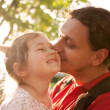 Father kissing daughter. Happy family outdoors. — Stock Photo