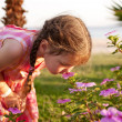 Stock Photo: Little girl smelling flowers on the beach.