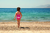 Little girl standing on beach in swimsuit and going to swim — Stock Photo