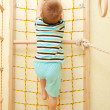 Little boy climbing on a rope net. — Stock Photo