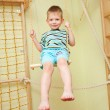 Little boy playing sports, swinging on swing — Stock Photo #27131023